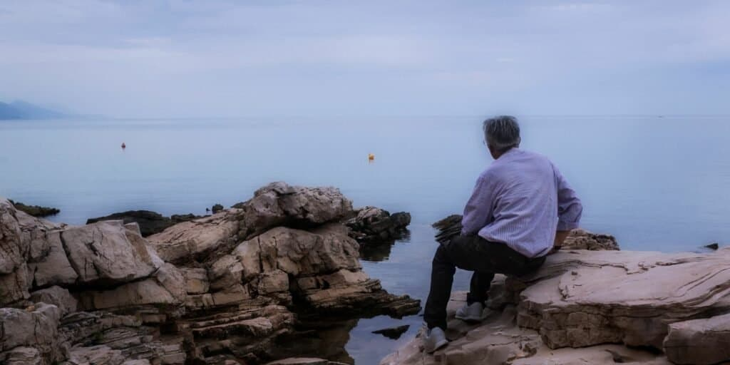 man looking out over the sea from the rocky shore