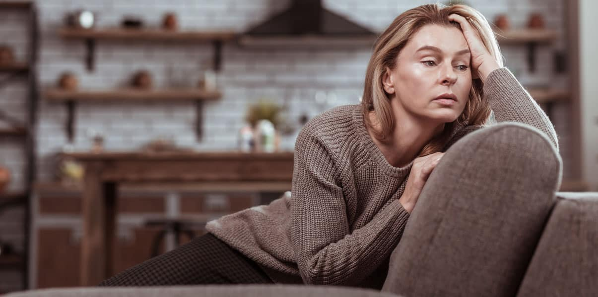 woman on couch looking sad