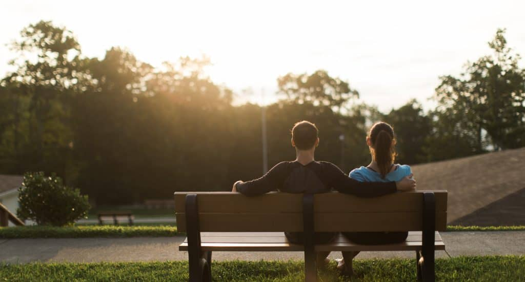 Two people sitting on bench at sunrise